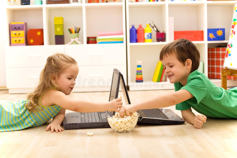 Miúdos com portáteis que comem a pipoca imagens de stock