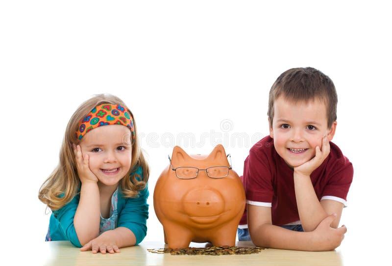 Miúdos com seu banco piggy perito imagem de stock