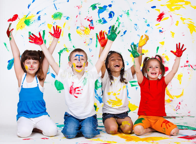 Miúdos com suas palmas e roupa pintadas fotos de stock royalty free