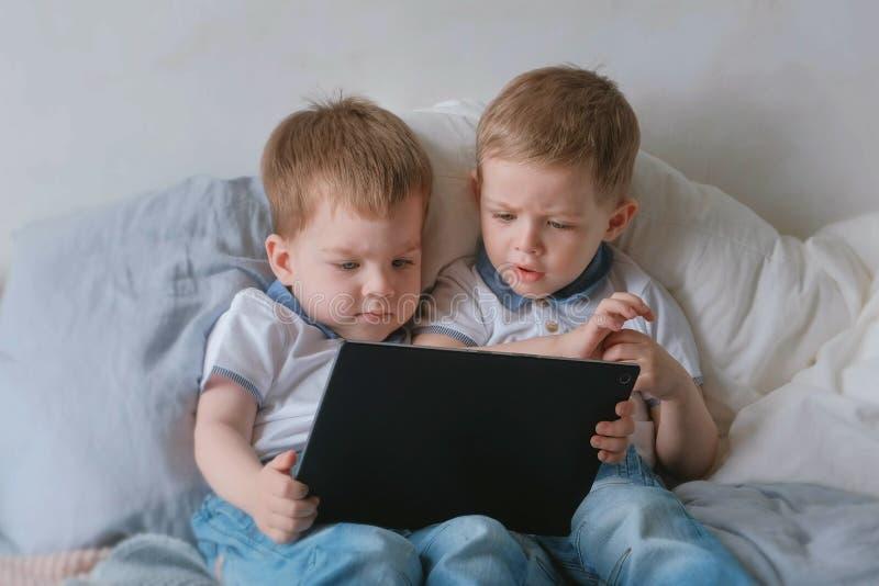 Miúdos com tabuleta Duas crianças dos gêmeos dos meninos que olham desenhos animados na tabuleta que encontra-se na cama foto de stock