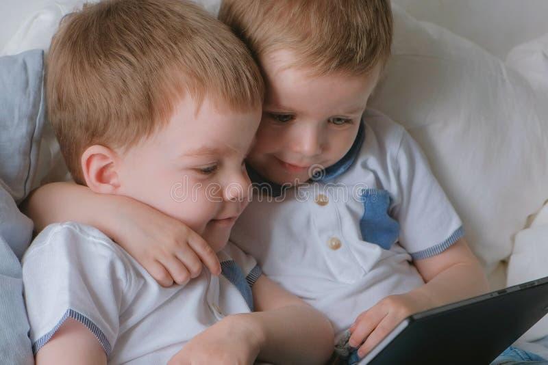 Miúdos com tabuleta Duas crianças dos gêmeos dos meninos que olham desenhos animados na tabuleta que encontra-se na cama fotografia de stock royalty free
