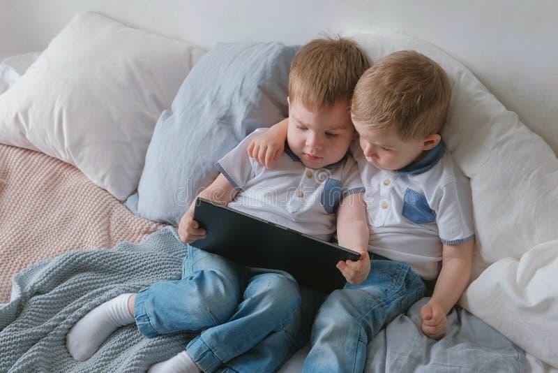 Miúdos com tabuleta Duas crianças dos gêmeos dos meninos que olham desenhos animados na tabuleta que encontra-se na cama fotos de stock royalty free