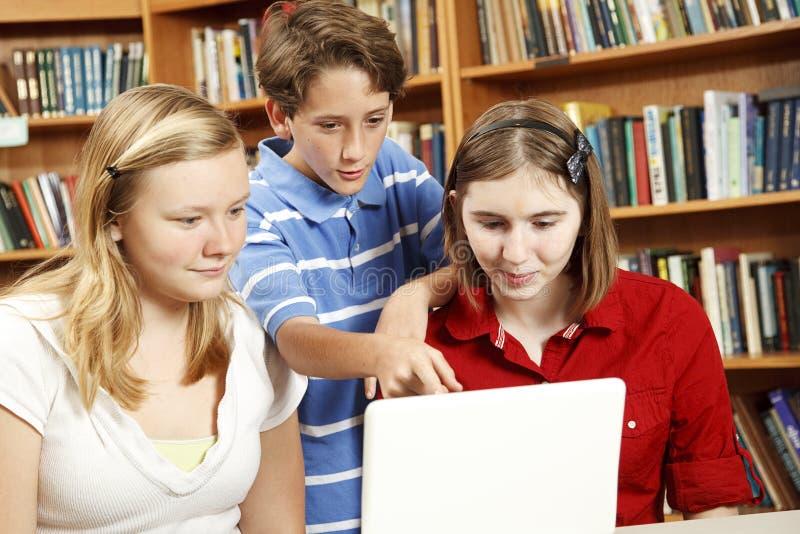 Miúdos da biblioteca no computador foto de stock