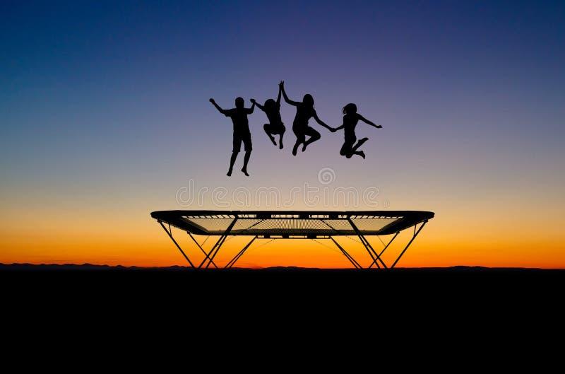 Miúdos do por do sol no trampoline foto de stock