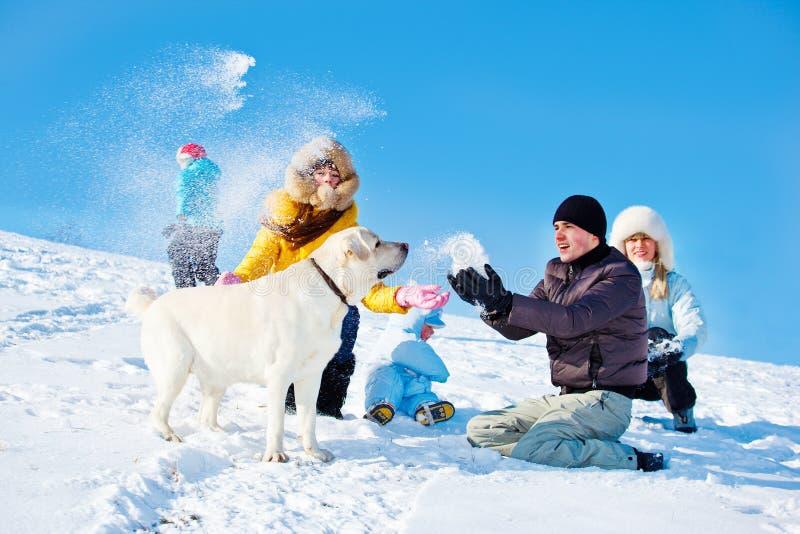Miúdos e pais que jogam a neve foto de stock