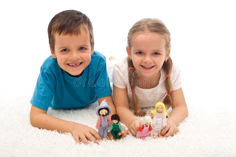 Miúdos felizes com os brinquedos no assoalho fotos de stock