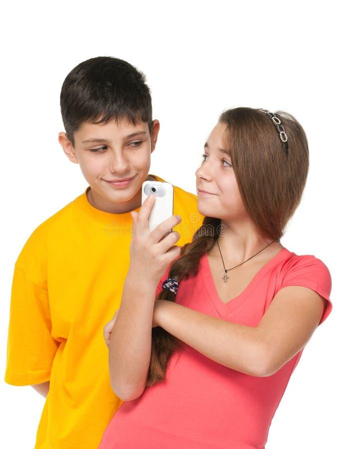 Miúdos felizes com um telefone de pilha foto de stock