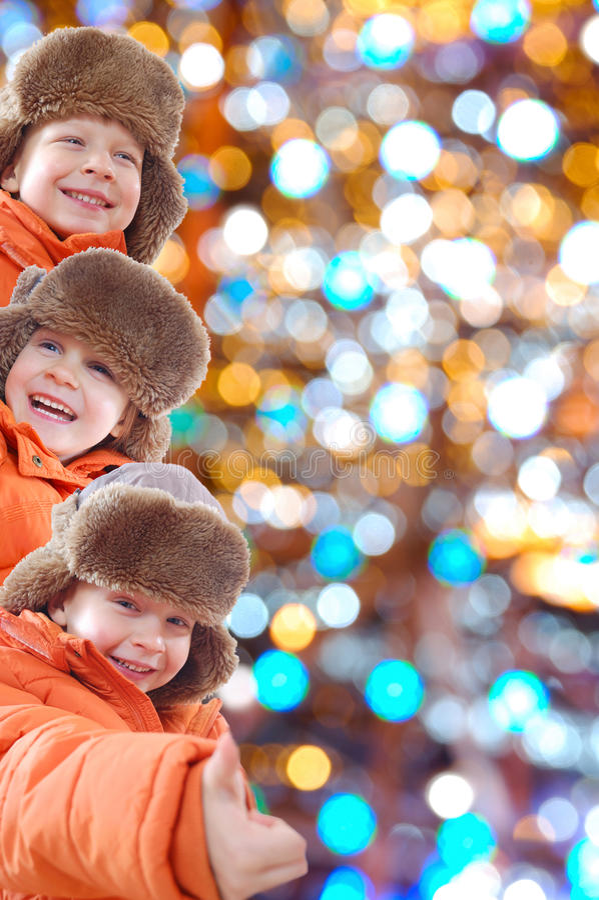 Miúdos felizes do inverno de encontro às luzes coloridas fotografia de stock royalty free