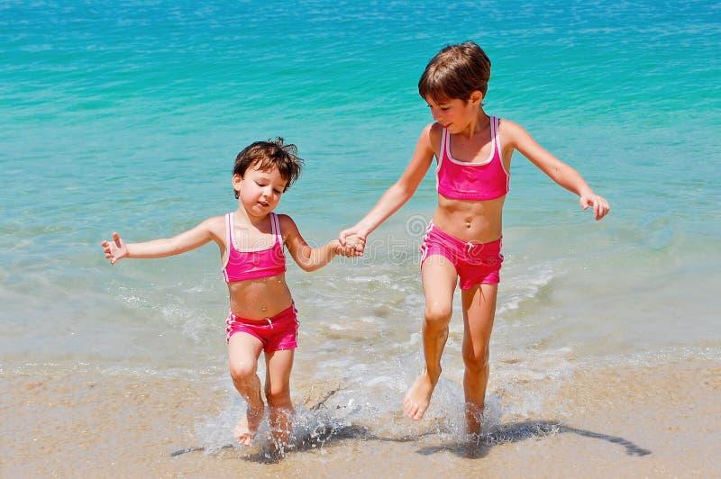 Miúdos felizes em férias da praia imagem de stock royalty free