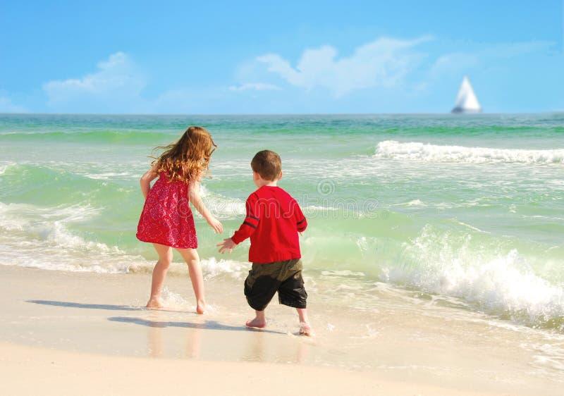 Miúdos felizes na praia bonita fotografia de stock