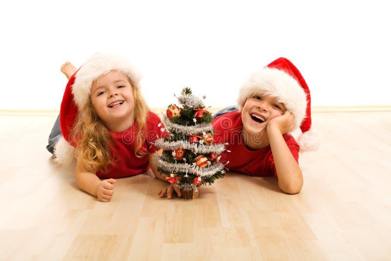 Miúdos felizes no assoalho no tempo do Natal foto de stock royalty free