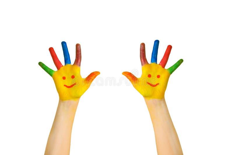 Miúdos felizes O ` s das crianças pintou as mãos com caras de sorriso imagens de stock
