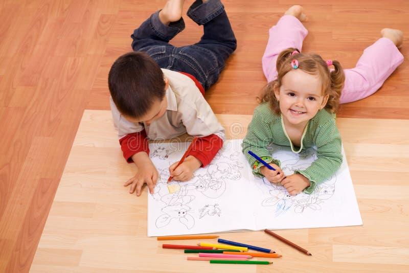 Miúdos felizes que colorem o livro do conto imagem de stock