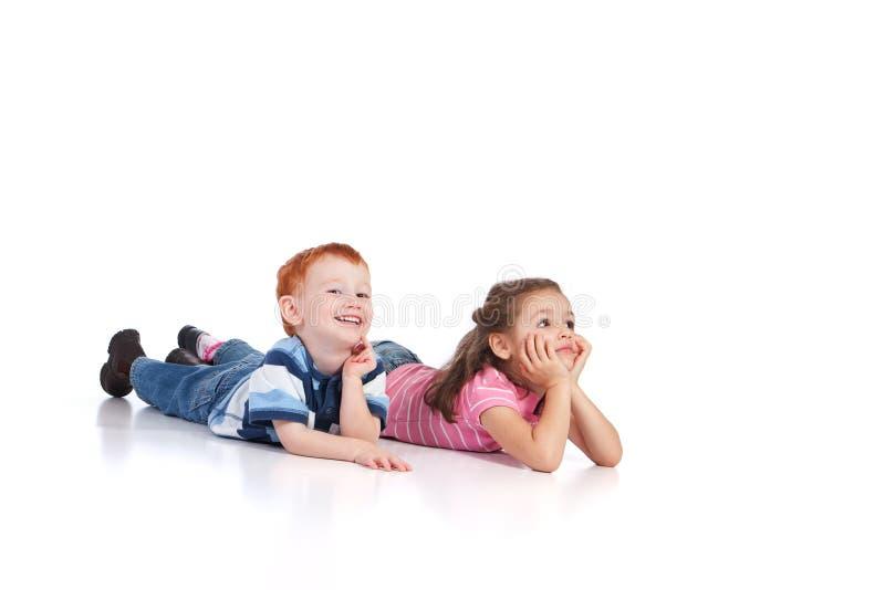 Miúdos felizes que encontram-se no assoalho fotografia de stock royalty free