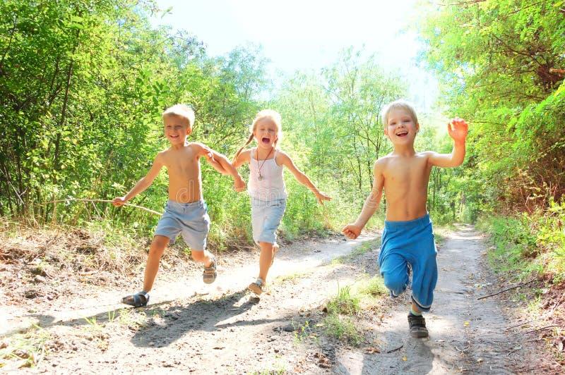 Miúdos felizes que funcionam nas madeiras imagem de stock royalty free