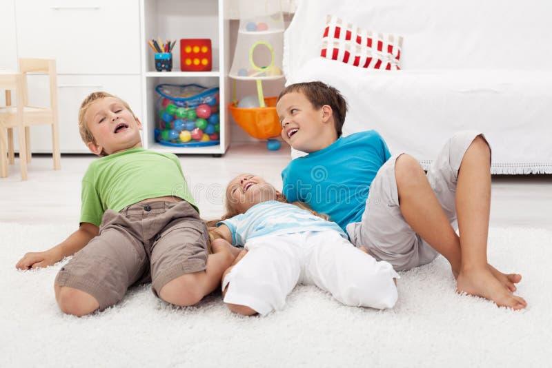 Miúdos felizes que jogam no assoalho foto de stock royalty free