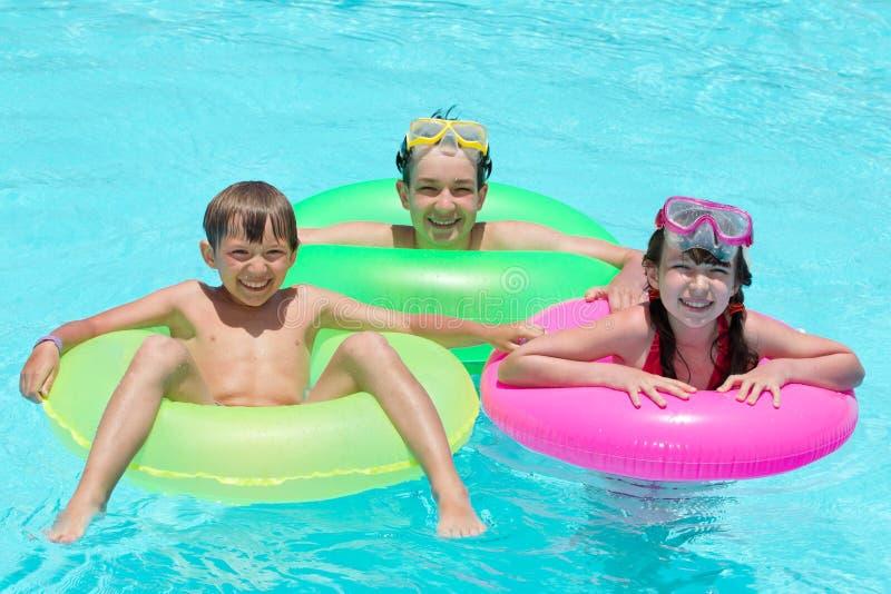 Miúdos felizes que nadam na associação fotografia de stock royalty free
