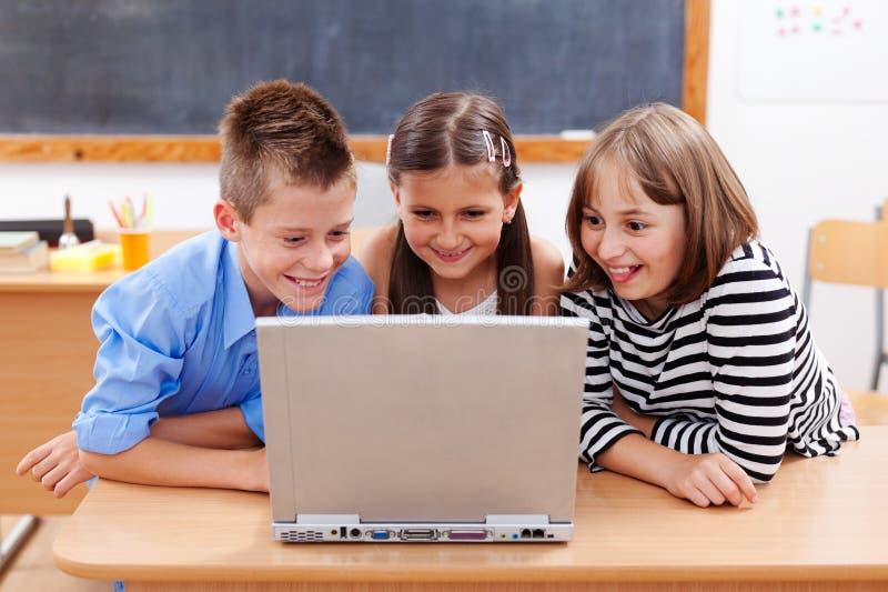 Miúdos felizes que olham o portátil fotografia de stock