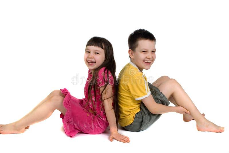 Miúdos felizes que sentam-se de volta à parte traseira fotos de stock royalty free