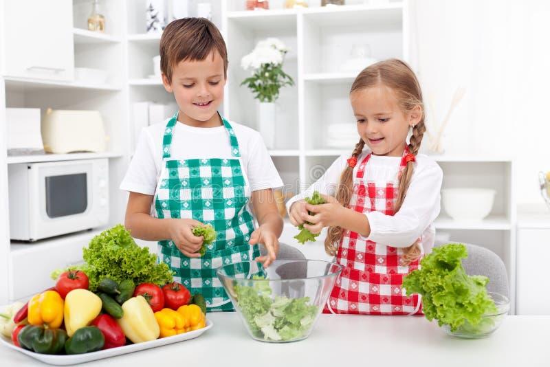 Miúdos na cozinha que prepara a salada foto de stock royalty free
