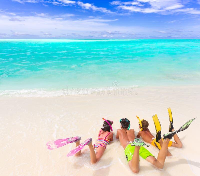Miúdos na praia com engrenagem do mergulho imagem de stock