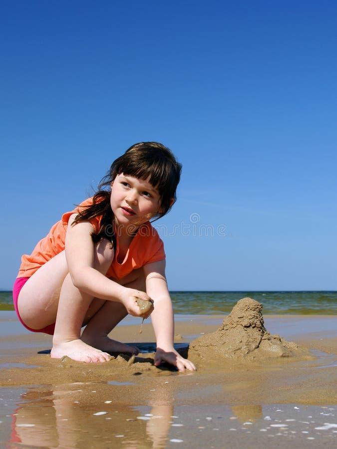 Miúdos na praia para fazer sandcastles fotografia de stock
