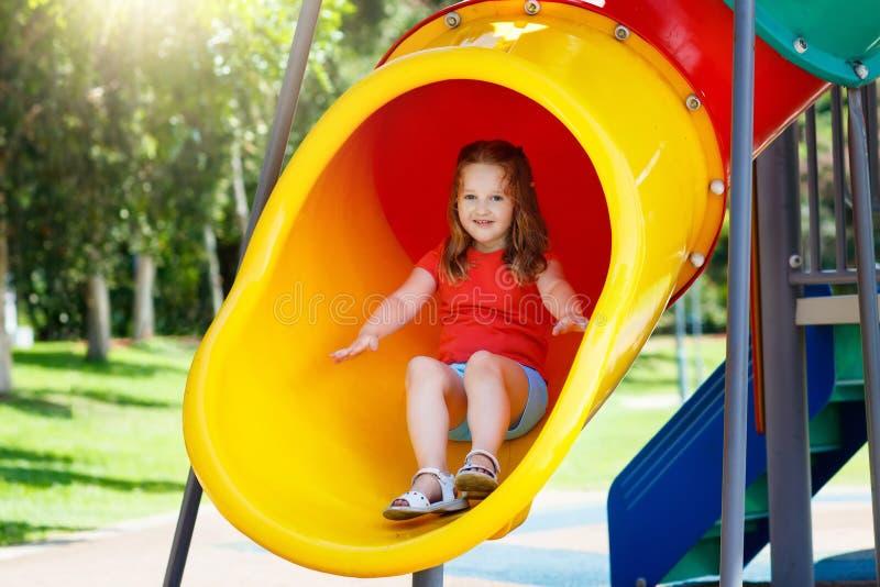 Miúdos no campo de jogos Jogo de crianças no parque do verão imagens de stock royalty free
