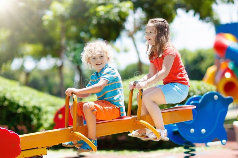 Miúdos no campo de jogos Jogo de crianças no parque do verão foto de stock royalty free