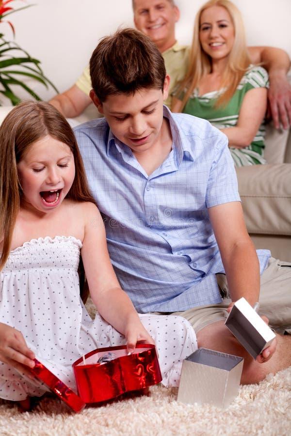 Miúdos que abrem presentes do Natal com pais imagens de stock royalty free