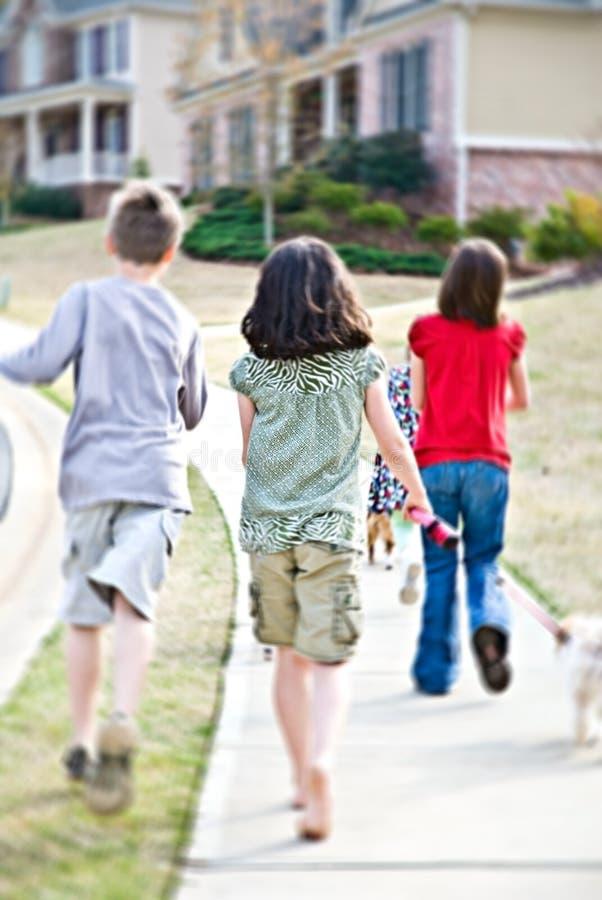 Miúdos que andam acima do passeio/borrão fotografia de stock