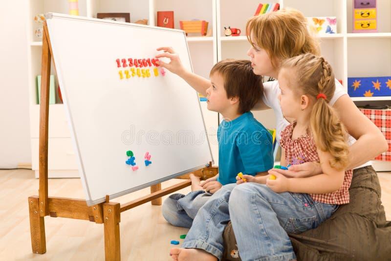 Miúdos que aprendem os números com sua matriz