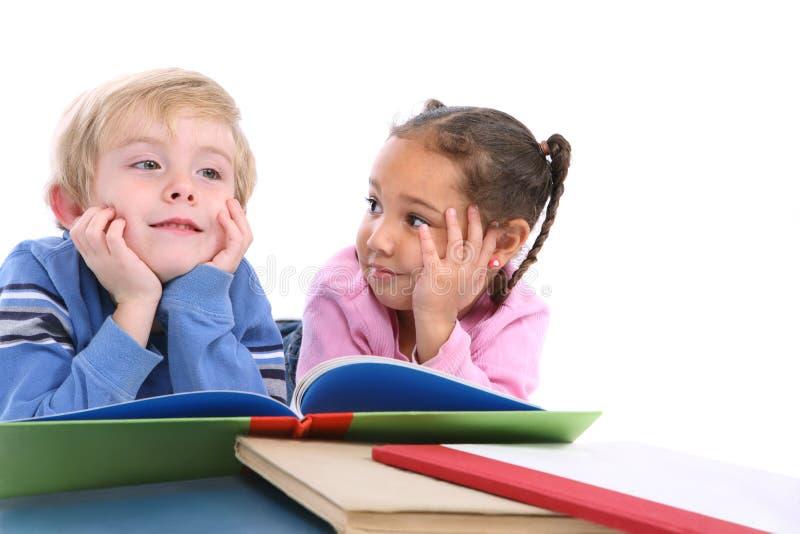 Miúdos que coloc e livros de leitura imagem de stock royalty free