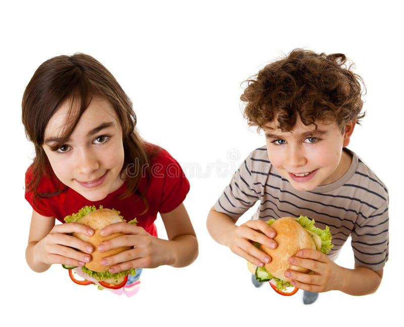Miúdos que comem sanduíches saudáveis imagem de stock