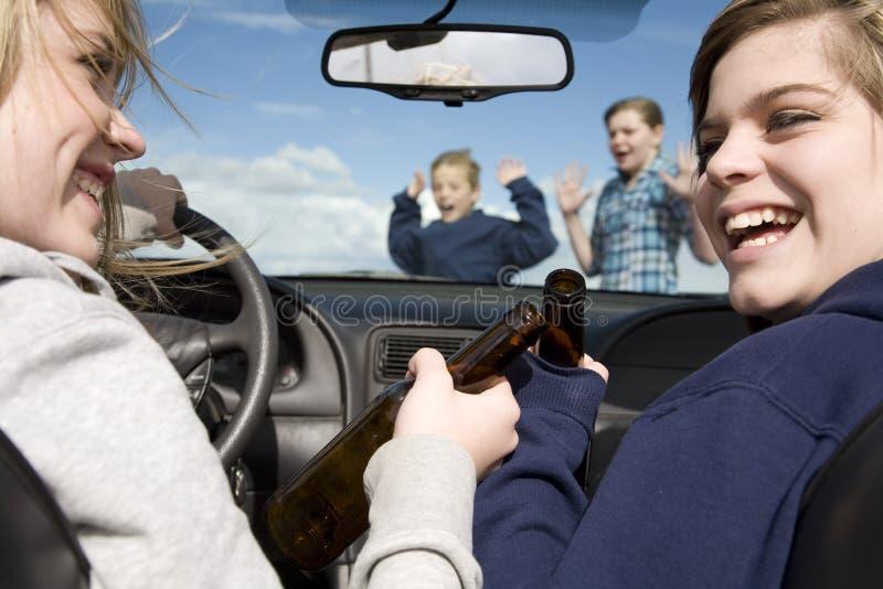 Miúdos que cruzam beber dianteiro do carro fotografia de stock