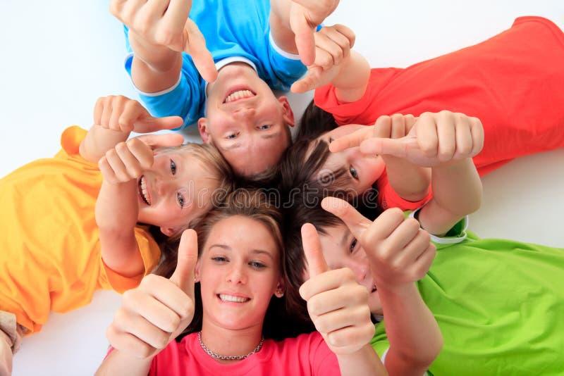 Miúdos que dão os polegares acima imagens de stock