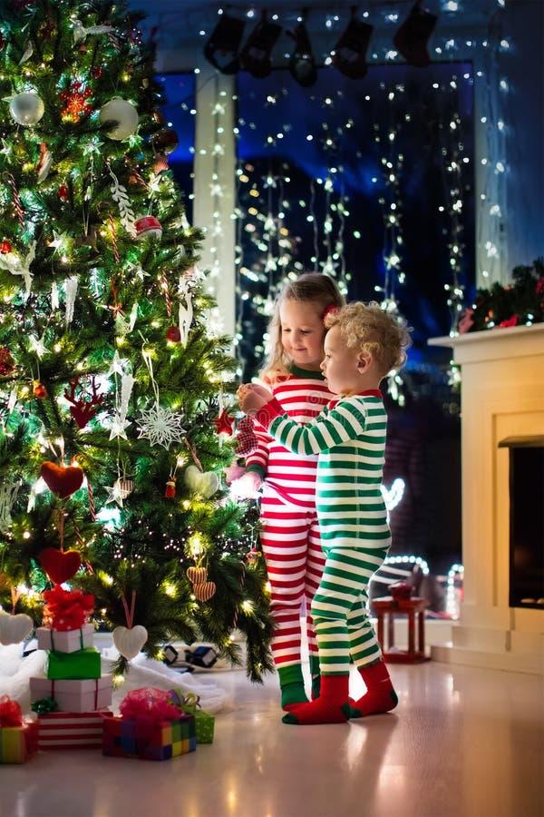 Miúdos que decoram a árvore de Natal imagens de stock royalty free