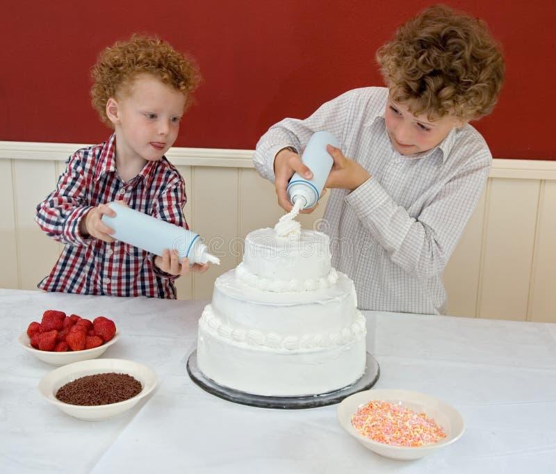 Miúdos que decoram o bolo foto de stock