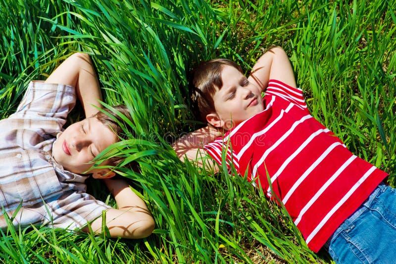 Miúdos que encontram-se na grama fotografia de stock