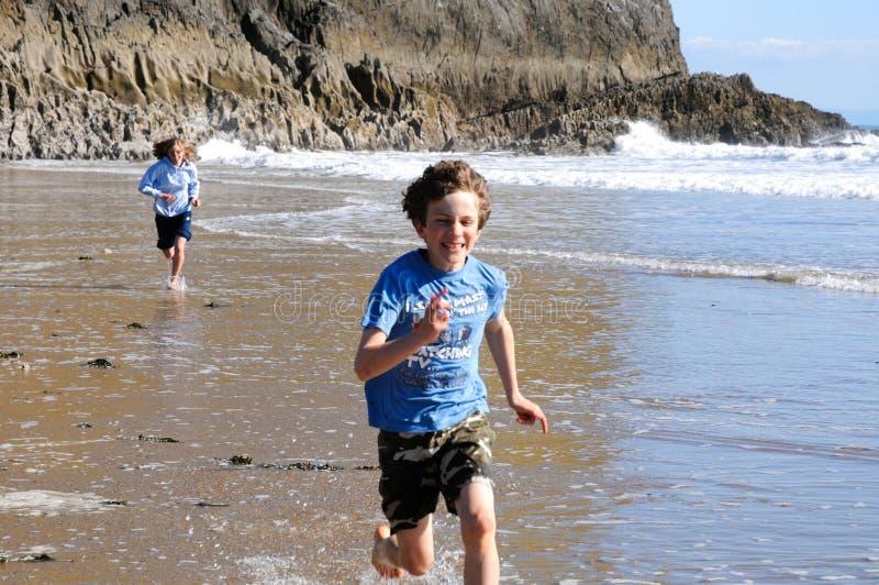 Miúdos que funcionam ao longo da praia imagem de stock