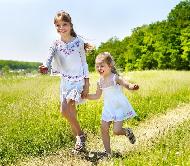 Miúdos que funcionam através da grama verde ao ar livre. fotos de stock royalty free