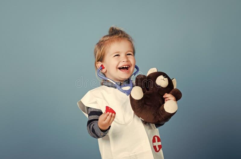 Miúdos que jogam com brinquedos Sorriso veterinário da criança feliz com o urso de peluche no fundo azul fotografia de stock royalty free
