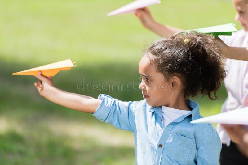 Miúdos que jogam com planos de papel imagem de stock