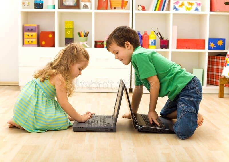 Miúdos que jogam em portáteis fotos de stock