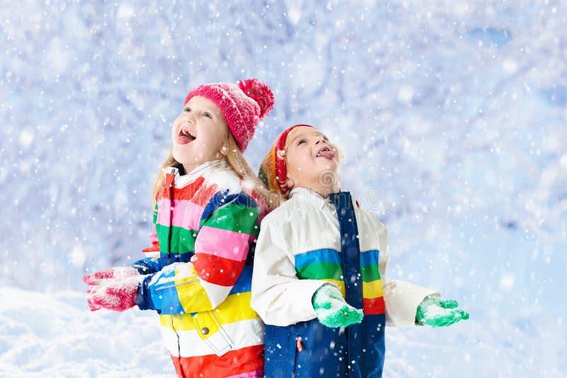 Miúdos que jogam na neve Jogo de crianças no inverno imagem de stock