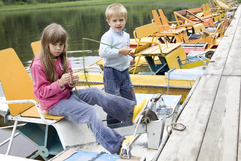 miúdos que jogam no catamarã amarelo no rio fotografia de stock