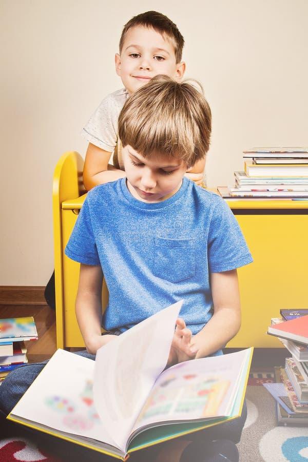 Miúdos que lêem um livro O menino lê uma história a seu irmão em casa imagem de stock royalty free