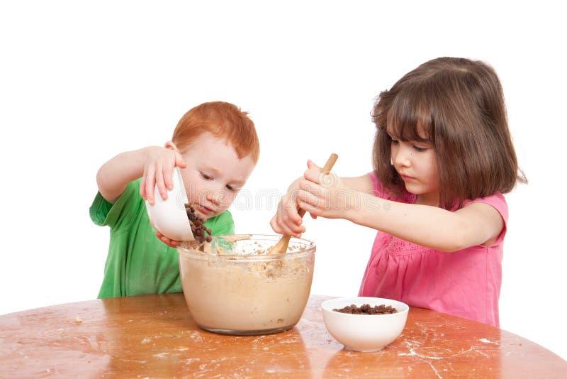 Miúdos que misturam e que derramam ingredientes do bolo imagem de stock