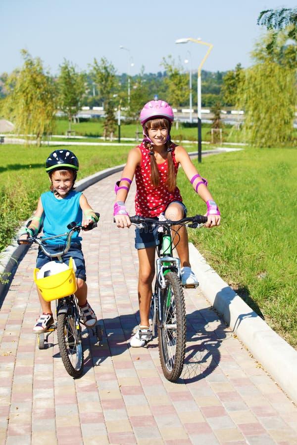 Miúdos que montam bicicletas no parque fotografia de stock royalty free