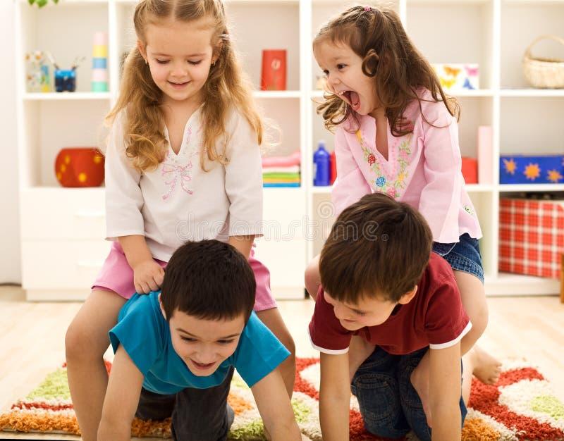 Miúdos que têm o divertimento em seu quarto imagens de stock