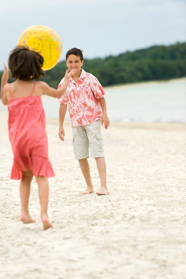 Miúdos que têm o divertimento na praia fotos de stock